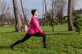 Young woman warming up and stretching the legs before running on a cold winter day in an urban park.