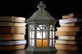Books and decorative lantern on table and dark background