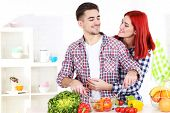 Happy couple preparing  vegetable salad in kitchen