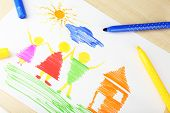 Drawing made by child with colorful pencils on wooden table background