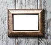 Golden photo frame on color wooden background
