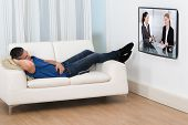 Man Lying On Sofa Watching Television