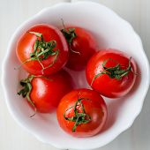 Fresh Tomatoes In White Bowl On Wooden Table