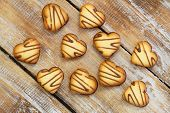 Heart shaped cookies scattered over rustic wooden surface