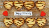 Happy Birthday card with heart shaped cookies and red hearts on rustic wooden surface