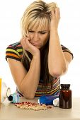 Woman With Pills Hands In Hair Look Down
