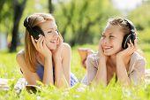 Young attractive girls in summer park wearing headphones