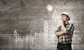 Young man builder looking thoughtfully at light bulb. Idea concept