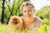 stock photo of dog park  - Young pretty girl in summer park with cute dog - JPG