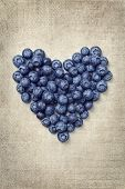 Heart from blackberries on a vintage background