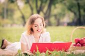 Young pretty woman in summer park reading book