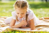 Little cute girl in summer park reading book
