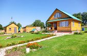 New Wooden Country House With Outbuildings In Summertime