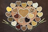 Grain food selection on a heart shaped wooden board and in porcelain bowls with wheat ears over lokta paper background.