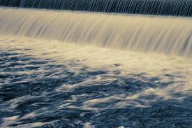 foto of water-saving  - Long exposure showing water patterns of dam water flowing - JPG