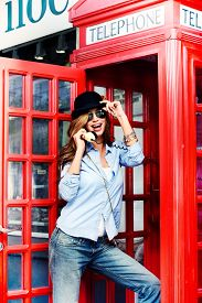 pic of phone-booth  - Pretty young woman talking on the phone in telephone booth - JPG