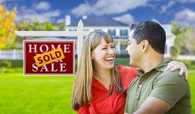 image of in front  - Happy Mixed Race Couple in Front of Sold Home For Sale Real Estate Sign and House - JPG