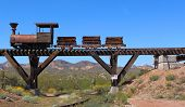 stock photo of wild west  - Old Wild West train with mining carts passing over an old wooden bridge with mountains - JPG