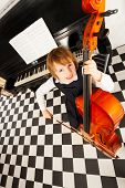 foto of cello  - Cheerful small girl in school uniform dress playing on the cello sitting near the piano and shelves with books view from above - JPG