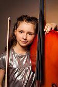 foto of gels  - Smiling girl with long hair holding the string to play violoncello over gel colored dark  background - JPG