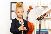 image of cello  - Cute small blond girl with flute standing near the cello in musical school - JPG