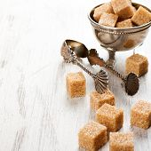 pic of tong  - Brown sugar cubes and metal sugat tongs on white wooden background - JPG