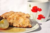 Plate of apple pie with fresh apples with honey and cup of tea