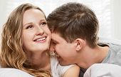 foto of laying-in-bed  - Happy smiling couple laying laughing in bed on light window background - JPG