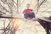 pic of adolescent  - Adolescent boy sitting on top of a playground swing set - JPG