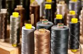 image of tailoring  - Background view of various colored yarns on bobbins at a tailor or clothing design studio in shades of greys and browns with focus to one in the foreground - JPG