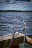 foto of rod  - Two fishing rods on a background of the river selective focus on the tips of the rods - JPG