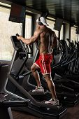 stock photo of elliptical  - Muscular Mature Man Doing Aerobics Elliptical Walker In Modern Fitness Center - JPG