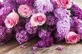 stock photo of purple rose  - Purple Lilac flowers with pink roses on wooden table - JPG