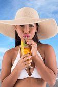 stock photo of filipina  - Beautiful woman in hat and bikini drinking summer cocktail - JPG
