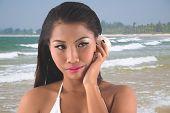 pic of filipina  - Beautiful Asian woman listening to the seashell - JPG