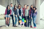 Постер, плакат: Happy teen girls and boys having good fun time outdoors Selective focus