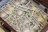 picture of yen  - A maroon briefcase stacked with Japanese yen notes - JPG