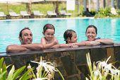 stock photo of swimming pool family  - Portrait of cheerful family of four in the swimming pool - JPG