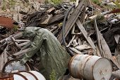 picture of gas mask  - Man with gas mask and green military clothes explores barrels after chemical disaster - JPG