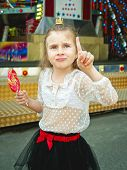 foto of amusement park rides  - cute little girl with lollipop at amusement park - JPG