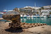 stock photo of bollard  - Bollard with a chain and rope in a port in Puerto Rico in Gran Canaria, Spain