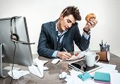 stock photo of loafers  - Young business man talking on the phone and writing down at his working place - JPG