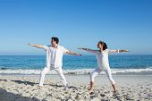 pic of beside  - Happy couple doing yoga beside the water at the beach - JPG