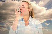 image of asthma  - Pretty blonde using an asthma inhaler against sky - JPG