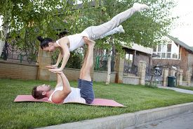 image of tantra  - An attractive man and woman practice tantra yoga on a grass before the house - JPG
