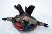 image of inflatable slide  - boy sledding down a snowy hill on a color inflatable sled