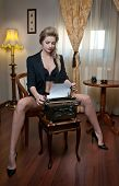 Attractive sexy blonde woman with black bra posing provocatively sitting on chair typing poster