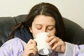 stock photo of cold drink  - woman with a cold drinking a hot tea - JPG