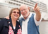 Senior Couple On Shore In Front Of Cruise Ship