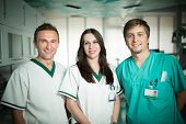 Постер, плакат: Young experienced doctor dentist standing along with his nurse assistants